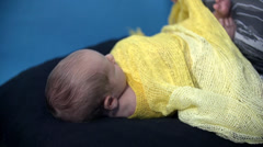 Covering a baby in yellowish kerchief Stock Footage