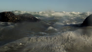 Stock Video Footage of Static and partially submerged shot of waves and rocks.