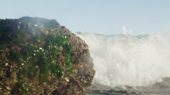 Static shot of a wave splashing over a mossy rock. Stock Footage