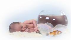 Baby lays nex to to a fish bowl Stock Footage