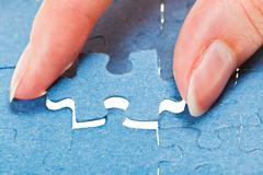 attaching the last blue piece of puzzle - stock photo