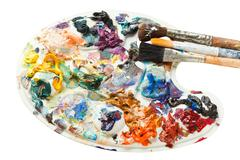 Artistic pallette with oil paints and paintbrushes Stock Photos