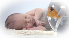 Baby lies next to a fish bowl looks at the fishes - stock footage