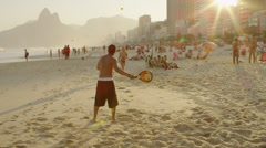 Slow motion shot of a couple playing tennis on Ipanema beach Stock Footage