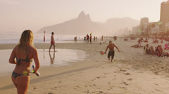 Slow motion, tracking shot of a couple playing tennis on Ipanema beach Stock Footage