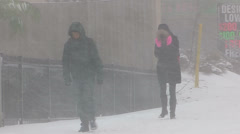 People walking in blizzard snow wind and cold weather in major winter storm Stock Footage
