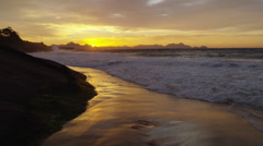 Slow-mo, static shot of killer waves hitting the beach and cliffs at Praia do Stock Footage