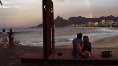 Camera pans to a rainbow in the distance at Ipanema Beach in Rio de Janeiro Stock Footage