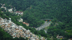 Eagles fly over a city bluff overlooking a tunneled intersection in Rio de Stock Footage