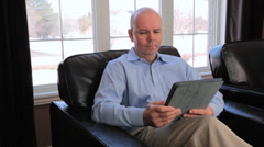 Mature Bald Man Reading On An iPad Sat In A Leather Arm Chair At Home Stock Footage