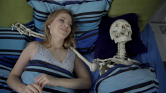 Young woman wakes up in bed next to a skeleton and hugs him Stock Footage