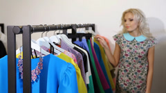 Woman in the shop looking at a clothes rack Stock Footage