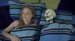 Woman is sleeping in the same bed as the human skeleton Stock Footage