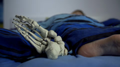 Human and skeleton's feet in the same bed Stock Footage