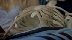 Close shot of woman reading to a skeleton Stock Footage