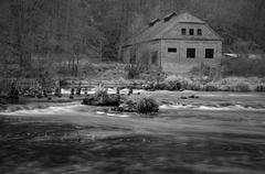An old house near by old demolished weir on the river Stock Photos