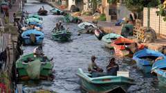 Men in fishing boats traveling along canal towards open ocean Stock Footage