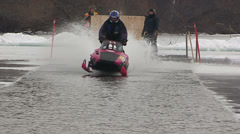 Snowmobiles and sleds racing across open water in puddle jumping event Stock Footage