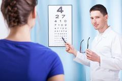 oculist examining patient - stock photo
