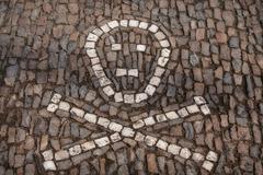 stone symbol skull and bones , touristic place kostnice - kutna hora. czech - stock photo