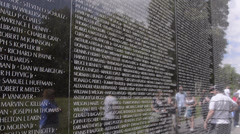 Tourists looking at friends name at reflections of hero names of war dead at - stock footage