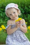 Coquettish little girl portrait with flowers Stock Photos