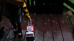 Child playing with Fire engine in the rain Stock Footage