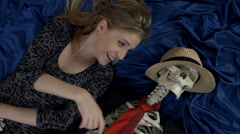 Female smiling out loud and touching the bones of the skeleton laying beside her Stock Footage