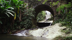 Tracking of a scenic stream flowing underneath an arched bridge. Stock Footage
