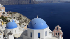 Beautiful village of Oia with white old buildings looking down at blue dome Stock Footage