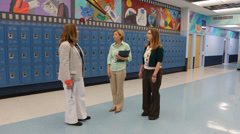 Principal talks with teachers and students by lockers Stock Footage