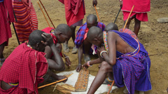 Amboseli National Park Kenya Africa safari Masai men playing Bao game on ground Stock Footage