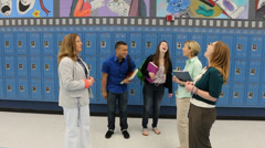 Principal, teachers and students talk in hallway and laugh Stock Footage