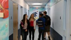 two sets of students males and females pass in hallway - stock footage