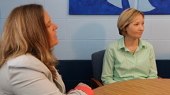Two teachers talking with principal pan left to right Stock Footage