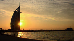 Worlds only 7 star hotel in Dubai UAE called the Burj Al Arab at sunset with Stock Footage