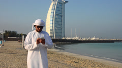 Emirate arab man with cell phone texting in front of Worlds only 7 star hotel in Stock Footage