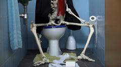 Skeleton sitting on the toilet having a number two Stock Footage
