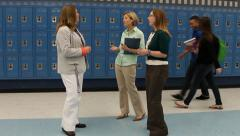 Principal, teachers and students talk in hallway Stock Footage