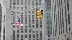 New York. Traffic lights and flag of the USA, against skyscrapers. Stock Footage