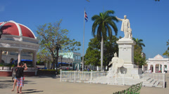 Trinidad Cuba main square with statue of Jose Marti and Cuban flag blowing Stock Footage