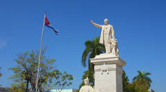 Trinidad Cuba main square with statue of Jose Marti and Cuban flag blowing - stock footage