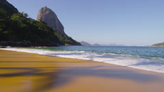 Slow motion of waves washing up at Red Beach in Rio. Stock Footage