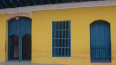Trinidad Cuba street with Cuban locals walking yellow building in old colonial Stock Footage