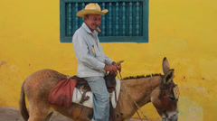Cuba Trinidad old man with cowboy hat with donkey for rides in center of old - stock footage