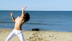 Professional dancer on the beach moving happy slow motion Stock Footage