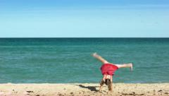 Little Girl In Pink Dress And Swimsuit Cartwheels Across Beach Stock Footage