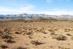 Semi-desert region with mountains and blue sky - stock photo