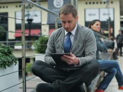 Businessman working on laptop and sitting on street bench, steadycam shot Stock Footage