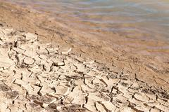 Contrast concept of dry cracked mud next to water Stock Photos